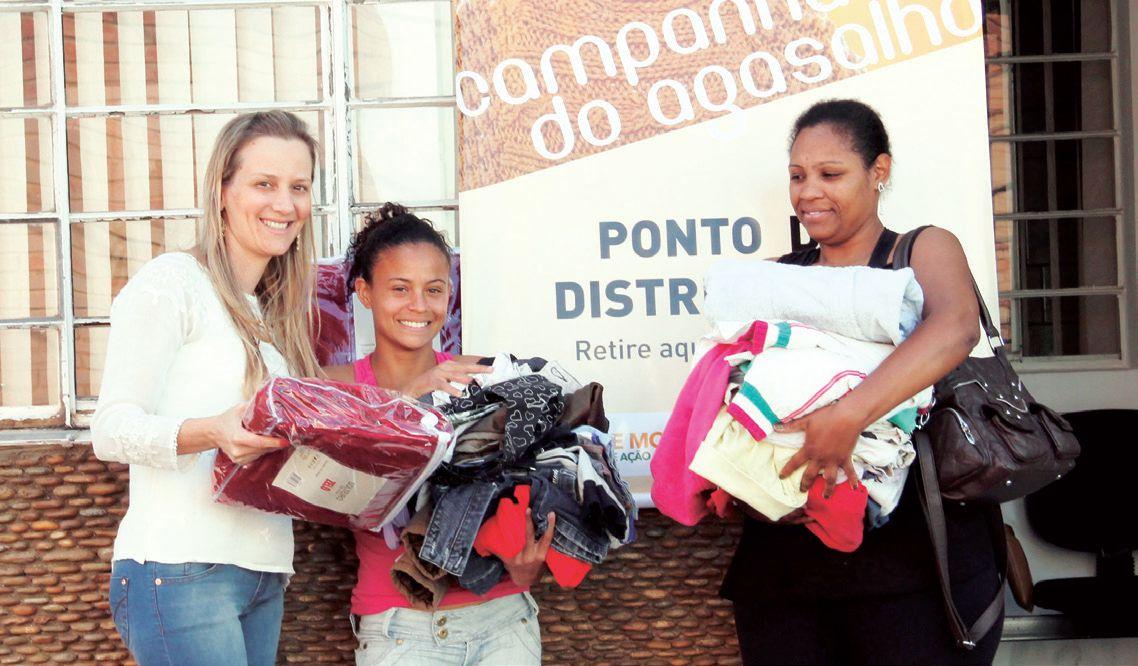 Presidente do Fundo Social Flávia Beckeforf (esquerda)entrega agasalhos para famílias carentes cadastradas.
