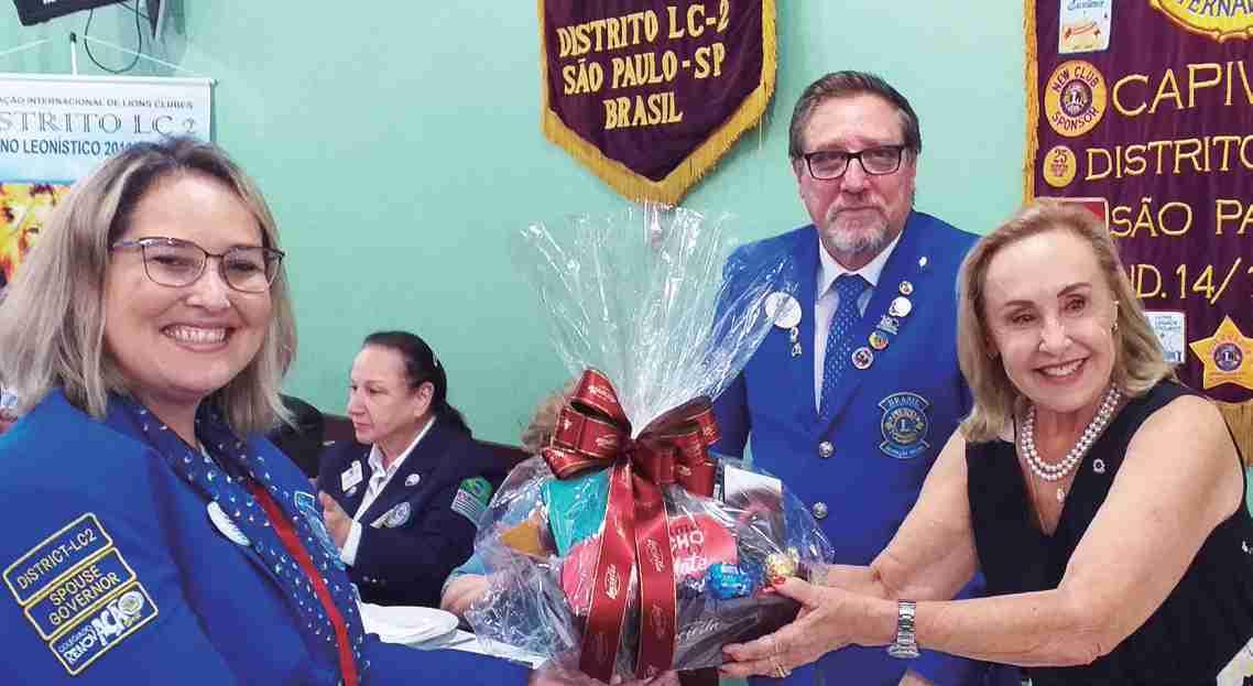 Observadas pelo governador Waldoylson, a sua esposa CaL Tatianna recebe lembrança de produtos capivarianos entregue pela presidente Maria Beatriz, durante reunião festiva comemorativa aos 57 anos do Lions e a visita oficial ao clube.